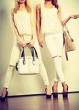 Dos señoras que sostienen los bolsos Imagenes de archivo