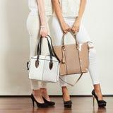 Dos señoras que sostienen los bolsos Fotos de archivo libres de regalías