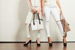 Dos señoras que sostienen los bolsos Imagen de archivo libre de regalías