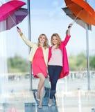 Dos señoras rubias que se divierten con los paraguas coloridos Fotos de archivo