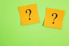 Dos signos de interrogación anaranjados en fondo verde Fotografía de archivo libre de regalías