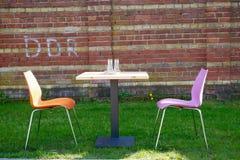 Dos sillas coloridas y una tabla del jardín Imagen de archivo libre de regalías