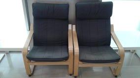 Dos sillas con el cojín negro están en un cuarto Fotos de archivo