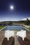 Dos sillas con la piscina cercana y la cubierta de madera Foto de archivo