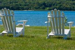 Dos sillas de Adirondack por el lago Imagen de archivo