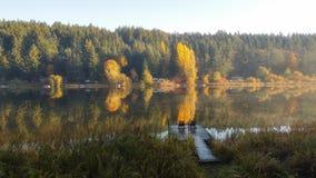 Dos sillas de Muskoka en un muelle en el lago fotos de archivo