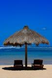 Dos sillas de playa bajo el toldo Imagenes de archivo