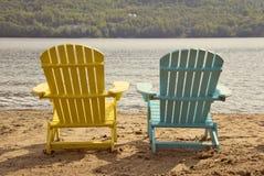 Dos sillas del adirondack en la playa arenosa por el lago Fotografía de archivo libre de regalías