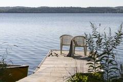 Dos sillas en una cubierta de madera con las cañas de pescar Fotografía de archivo