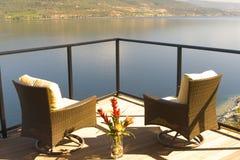 Dos sillas lujosas en una cubierta de sol de la orilla del lago Imagen de archivo libre de regalías