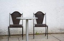Dos sillas oscuras contra la pared blanca que acoge con satisfacción a huéspedes Imagen de archivo libre de regalías