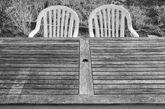 Dos sillas plásticas y una tabla de madera en el huerto Foto de archivo