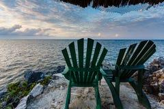 Dos sillas verdes vacantes aguardan a visitantes para relajar y para disfrutar de puesta del sol del punto rocoso en el Caribe Fotografía de archivo libre de regalías