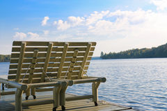 Dos sillones se sientan en un muelle en verano al lado de un lago Imágenes de archivo libres de regalías