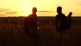 Dos siluetas de los turistas dos turistas en la puesta del sol se están colocando en las tarjetas de observación del campo en el  almacen de metraje de vídeo