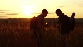 Dos siluetas de los turistas dos turistas en la puesta del sol se están colocando en las tarjetas de observación del campo en el  metrajes