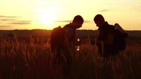 Dos siluetas de los turistas dos turistas en la puesta del sol se están colocando en las tarjetas de observación del campo en el  almacen de video