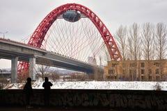 Dos siluetas humanas en el fondo del puente del camino con un arco rojo foto de archivo