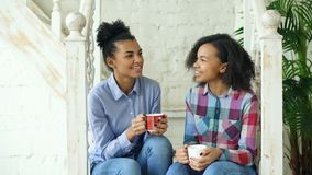 Dos sistres rizados afroamericanos de las muchachas que se sientan en las escaleras se divierten que ríe y que charla juntos en c Foto de archivo