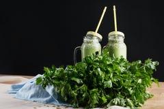 Dos smoothies vegetales Los tarros de albañil de proteína sacuden en un fondo de la tabla Cóctel nutritivo del veggie con perejil imagen de archivo libre de regalías
