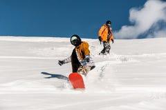 Dos snowboarders en la ropa de deportes que monta abajo de la cuesta de montaña Foto de archivo