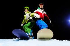 Dos snowboarders que llevan la máscara de esquí en la noche Imagen de archivo