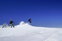Dos snowboarders saltan en parque de la nieve en la estación de esquí en invierno soleado Foto de archivo
