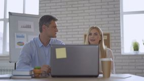 Dos socios comerciales adultos trabajan adentro de la oficina en el ordenador 4K almacen de video