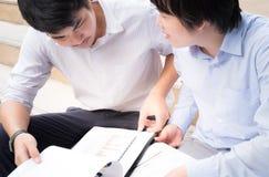 Dos socios comerciales contentos que discuten el modelo comercial With Pap Imagen de archivo