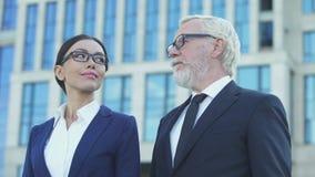 Dos socios comerciales que colocan al aire libre el centro de la oficina, compartiendo experiencia almacen de video
