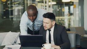 Dos socios comerciales que discuten activamente su proyecto de inicio que se sienta en café elegante Hombre de negocios barbudo q metrajes