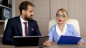 Dos socios comerciales que discuten y que analizan negocio de la estrategia en los tableros con las cartas metrajes