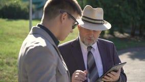 Dos socios comerciales que hablan y que usan las tabletas al aire libre 4K