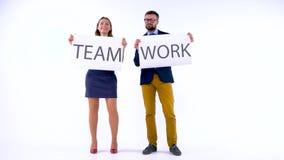 Dos socios comerciales que presentan en el estudio con los carteles en manos El concepto de trabajo en equipo almacen de metraje de vídeo