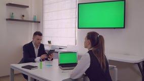 Dos socios comerciales que se sientan en el escritorio en oficina moderna metrajes
