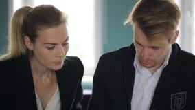 Dos socios discuten el proyecto de funcionamiento que se sienta en oficina en tiempo del día almacen de metraje de vídeo