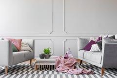 Dos sofás con la porción de almohadas y de mesa de centro con la planta en pote, los floreros de cristal y las tazas de café en l foto de archivo