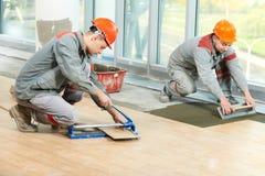 Dos soladores en la renovación industrial del embaldosado del suelo Fotos de archivo