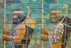 Dos soldados con los arcos y lanzas, pared modelada de cerámica de la ciudad Babilonia Fotos de archivo libres de regalías