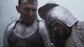 Dos soldados medievales en la armadura, cansada bajo la lluvia después de la batalla almacen de video