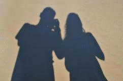 Dos sombras en la superficie arenosa mojada Fotografía de archivo
