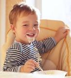 Dos sonrisas del muchacho de los años y gachas de avena de la consumición. Imagen de archivo libre de regalías