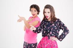 Dos sorprendieron a las mujeres jovenes con las bocas abiertas que señalaban lejos Foto de archivo libre de regalías