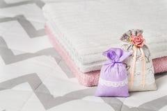 Dos sospecharon las bolsitas que se inclinaban en dos toallas en cama Bolsas fragantes de la lavanda para el diseño interior y el Fotos de archivo libres de regalías