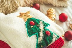 Dos suéteres del invierno puestos en una cama con las almohadas y las decoraciones del Año Nuevo imagen de archivo