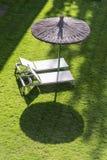 Dos sunbeds vacíos en un campo verde con un paraguas, alistan para que la gente relaje y tome un sunbath imagenes de archivo
