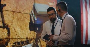 Dos técnicos que miran la pantalla en sala de control