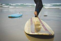 Dos tablas hawaianas en la arena de la playa con las ondas en la parte inferior foto de archivo