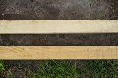 Dos tablones de madera mienten paralelo en la tierra y la hierba en el jardín foto de archivo