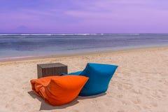 Dos taburetes y una tabla de mimbre que se coloca en una playa Foto de archivo